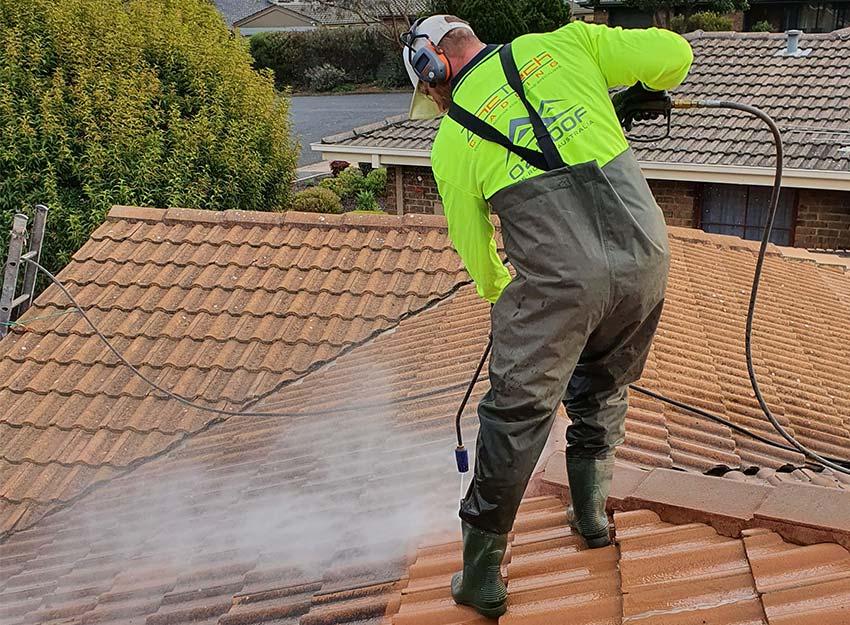 man on roof terracotta restoration