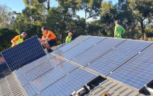 trades people removing solar panels from roof